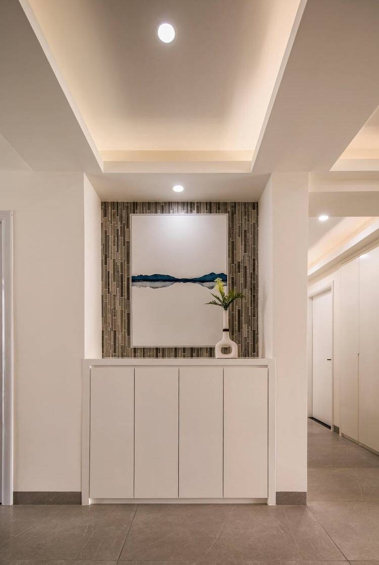 入户玄关使用灰木纹大理石马赛克做背景,点缀留白抽象画,空间简洁而